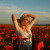 Blonde woman in a field of red flowers